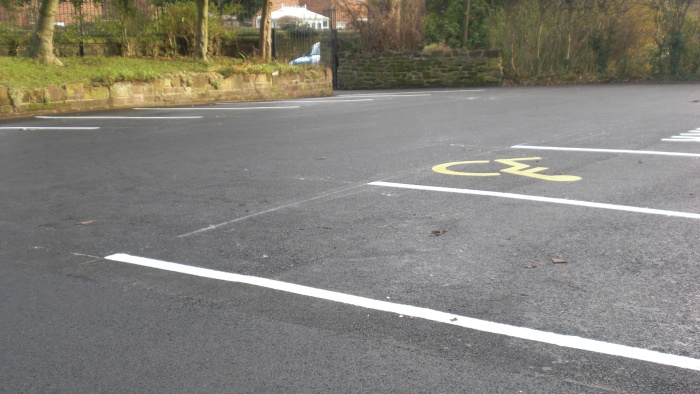 close up of an asphalt car park with disabled spots