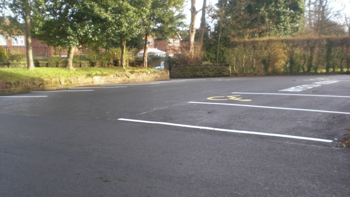 asphalted car park with disabled bay on sunny day