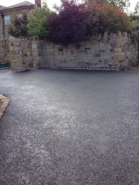 asphalt driveway and a cobble wall