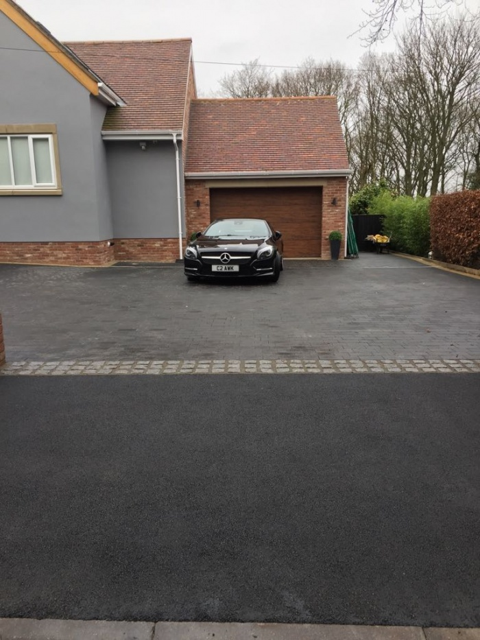 recently surfaced macadam driveway with parked car