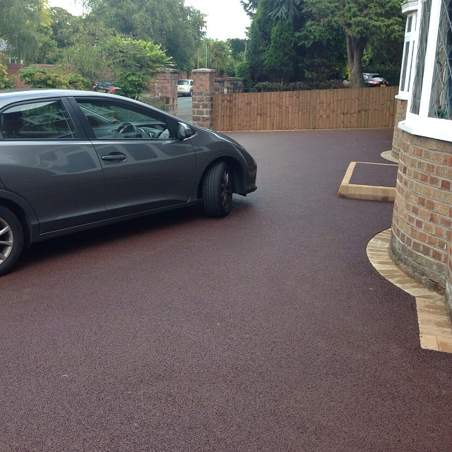 red tarmac driveway with car parked on top